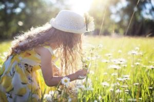 girl enjoying outdoor learning by picking flowers