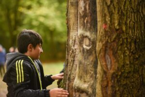 boy feeling tree for outdoor learning purposes